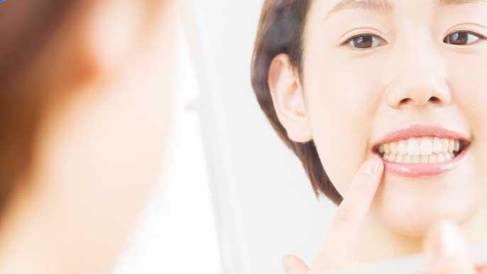 鏡を使って自分の歯の白さを確認してる女性